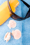 Towel, sunglasses and lotion Stock Image