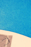 Towel and Sunglasses by Pool Stock Photos