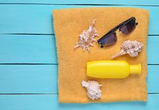 Towel with sunscreen, cockleshells, sunglasses on blue wooden boards. The concept of a resort beach holiday, top view. stock photos