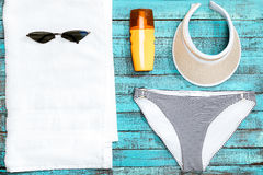 Towel, swimming pants, sunglasses and sun cream on table Stock Images