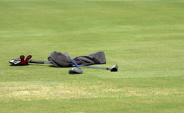 Towel and two golf clubs. Wet towel and two golf clubs lying on the green grass at the golf course. Sunny day Royalty Free Stock Photography
