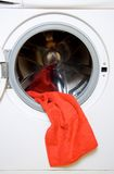Towel and washing machine. Red towel hang on door of the opened washing machine Stock Images