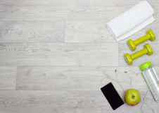 Towel, weights, water bottle, apple and phone on wooden background Royalty Free Stock Photo