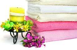 Towels. Stack of clean colorful towels with candle and flowers isolated on white background Stock Photos