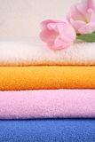Towels. Stack of colorful towels with pink tulips close-ups stock images