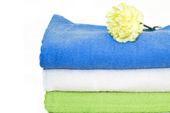 Towels. Colorful towels and yellow carnation on the white Stock Photo