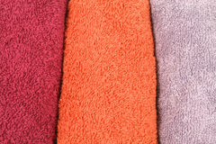 Towels background. Background of three colorful towel rolls - orange, maroon and violet Stock Photo