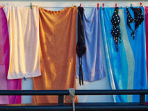 Towels and bathing swim suits drying on the clothesline Royalty Free Stock Image