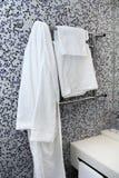 Towels and bathrobe on heated towel rail Stock Photography