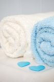 Towels with blue valentine hearts. Rolled bathroom towels, sitting on toilet with blue scattered hearts Royalty Free Stock Image