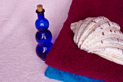 Towels,bottle and shell. Colored  towels with a blue glass bottle and a shell Royalty Free Stock Image