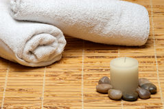 Towels with candle, rocks on bamboo mat Stock Photo