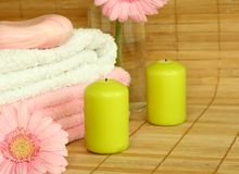 Towels, candles, soap and pink gerber. Stock Photo