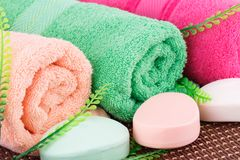 Towels. Colorful rolled towels with leaves and soaps closeup picture Royalty Free Stock Image
