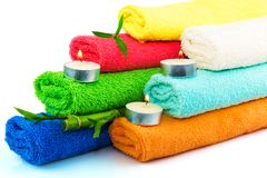 Towels with candles and bamboo. Towels of different colors with candles and bamboo on white Stock Photos