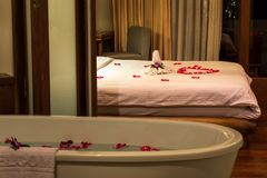 Towels, Flowers And Red Rose Petals Decorations On The Bed, Flowers And Petals In Bathtub, Concept Of Honeymoon Royalty Free Stock Photo