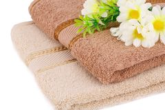 Towels and flowers. Folded towels and flowers closeup picture Royalty Free Stock Images