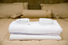 Towels on hotel bed. White towels piled on the hotel bed Royalty Free Stock Photography