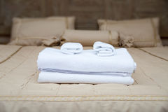 Towels on hotel bed. White towels piled on the hotel bed Stock Photos