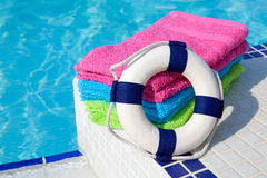 Towels and life buoy near the swim pool Royalty Free Stock Photos