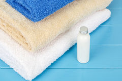 Towels with little bottle of shampoo on a blue wooden background Royalty Free Stock Images