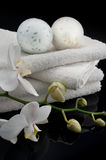 Towels with orchid and bath balls. White towels with orchid on black bacground, mirrored stock photo