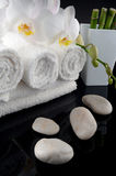 Towels with orchid and stones. White towels with orchid on black bacground, mirrored stock photo