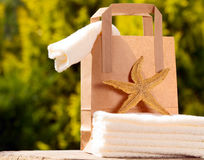 Towels with paper bag and sea star Royalty Free Stock Photos