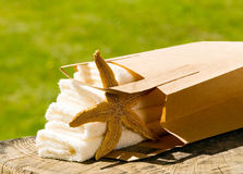 Towels with paper bag and sea star Royalty Free Stock Photography