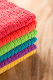 Towels in rainbow colors on brown wooden table Stock Image