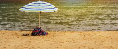 Colorful beach umbrella. Towels and sandals under colorful beach umbrella on beach Stock Image