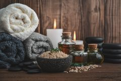 Spa concept. Towels with sea salt, massage oil in vintage bottle, candles and stones for stone massage on wooden background Royalty Free Stock Photos