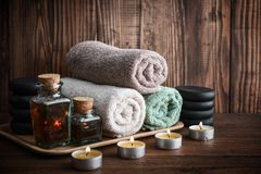Spa concept. Towels with sea salt, massage oil in vintage bottle, candles and stones for stone massage on wooden background Stock Photos