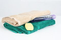 Towels and soap still life. Close up of two folded towels with bar of soap and liquid soap bottle, white background royalty free stock photo