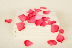 Towels and soap under petals of roses Royalty Free Stock Photography