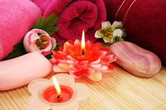 Towels, soaps, flowers, candles. Towels, soaps, flowers and candles on mat background Royalty Free Stock Image