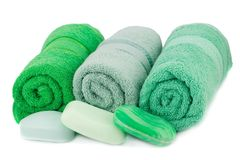 Towels and soaps. Rolled green towels  and soaps isolated on white background Stock Image