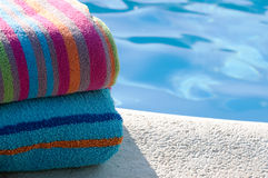 Towels by swimming pool. Colourful towels folded by pool Royalty Free Stock Photography
