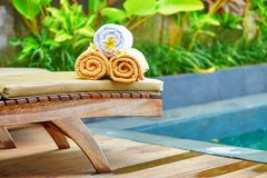 Towels with white frangipani flowers near the pool Stock Photos