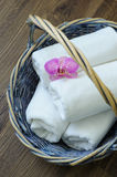 Towels in a wicker basket. Orchid flower with towels in a wicker basket on a wooden background royalty free stock photos