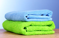 Towels on wooden table on blue background Royalty Free Stock Image
