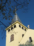 Tower. An old yellow church tower and branches stock photo