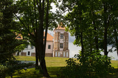 Tower of ancient castle through the trees of the park Stock Image