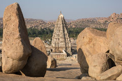 Tower of an ancient temple. Tower above the main entrance to the ancient Hindu temple against the background of the rocks Stock Photo
