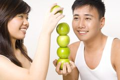 Tower of Apples. A healthy looking couple make a tower from green apples Stock Photo