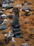 Tower of Beach Pebbles upright on sand. BEACH Stones and Pebbles different sizes and shapes. Still life. Sea worn and battered stones and pebbles in a tower Stock Photo