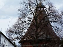 The Tower Behind the Tree. Pointy tower in gray and rusty color behind a large tree with light blue sky above - abstract stock photography