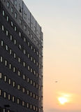 Tower block at sunset with helicopter in sky. Stock Photos