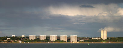 Tower Blocks on a Stormy Day. A line of tower blocks in Woolston, Southampton, looking over Southampton Water. A break in the clouds casts the sun over the Stock Image