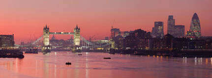 Tower Bridge and city of London with deep red suns. A panoramic view of Tower Bridge and the City of London with deep red sunset Royalty Free Stock Images